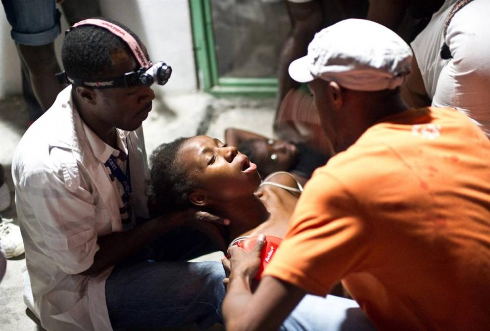 1. Женщина теряет сознание на руках медика в больнице округа Петионвилль в Порт-о-Пренс, Гаити, 12 января. Ранее землетрясение в 7.0 баллов прошлось по Карибским островам, вызвав всеобщие разрушения. (Frederic Dupoux / Getty Images)