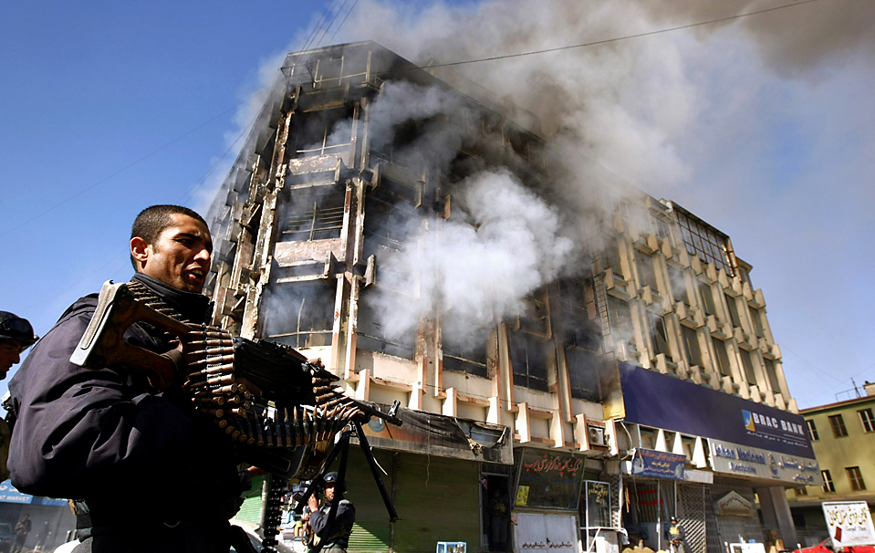 5. Полицейский охраняет торговый центр, где боевики «Талибана» вели перестрелку со службами безопасности в Кабуле. Боевики взрывали бомбы и пытались захватить здания. Погибло, по меньшей мере, 12 человек, включая семь боевиков. (Omar Sobhani/Reuters)