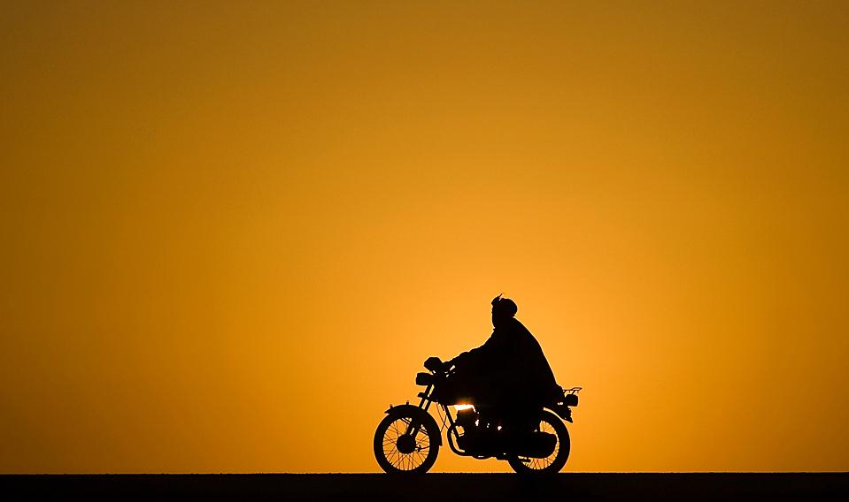1. Человек едет на мотоцикле на закате в провинции Нимроз, Афганистан. (Marko Djurica/Reuters)