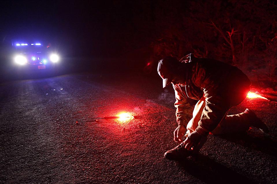 3. Брайан Эббитт завязывает шнурок на блокированном полицейскими участке дороги рядом с домом, где были застрелены восемь человек, в Аппоматтоксе, штат Вирджиния. Убийца – 39-летний Кристофер Спейт сдался рано утром в среду. Полиция сообщила, что он прятался в лесу. На нем был пуленепробиваемый жилет. (Steve Helber/Associated Press)