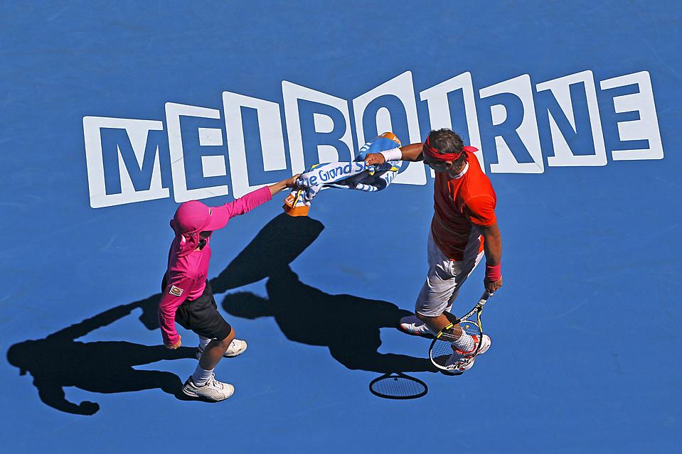 5. Испанец Рафаэль Надаль берет полотенце у мальчика во время игры против словака Лукаса Лако на теннисном турнире «Australian Open» в Мельбурне. Встречу выиграл Надаль. (Mark Baker/Associated Press)