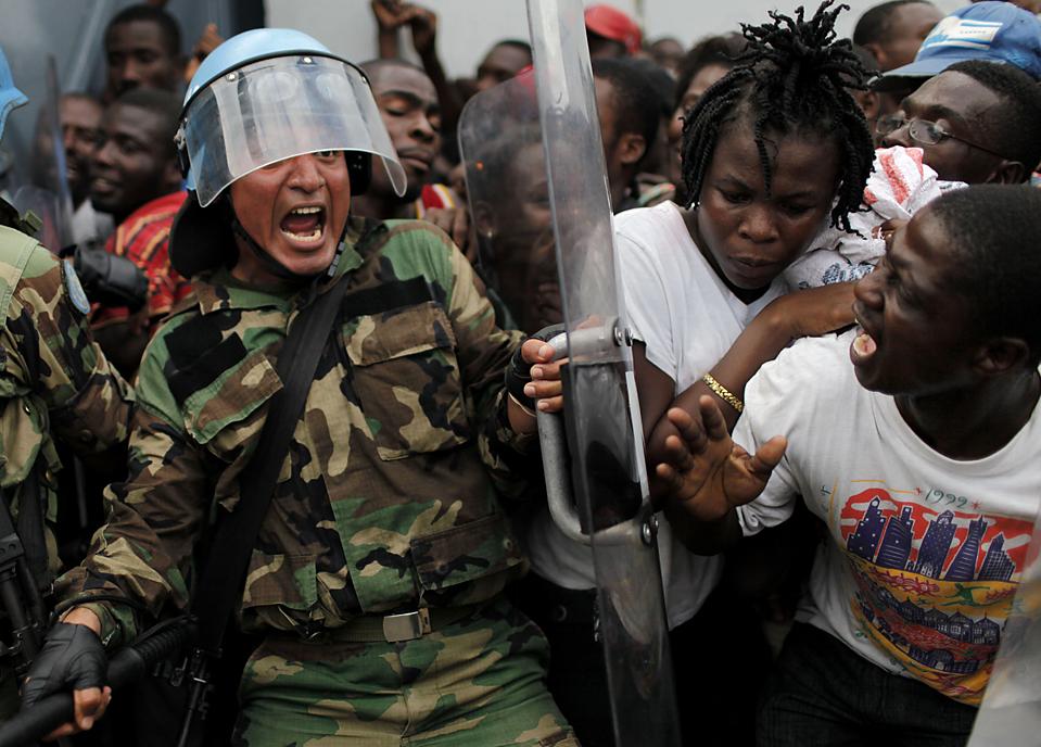 8. Перуанский миротворец кричит, пытаясь сдержать толпу во время раздачи еды в Порт-о-Пренс. Совет безопасности ООН проголосовал за выделение еще 2000 миротворцев и 1500 полицейских для контроля. В среду новый толчок в 6.1 баллов ударил по и без того разрушенной территории Гаити. (Ariana Cubillos/Associated Press)