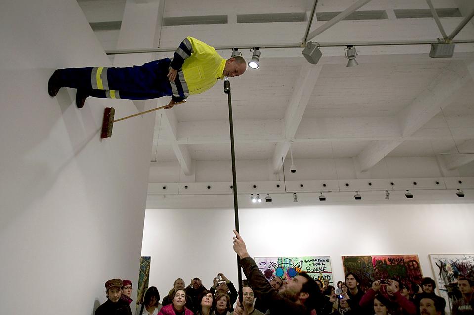 9. Мужчина дает попить немецкому художнику Йохану Лорберу, которого прикрепили к стене во время акции «Пролетарская фреска» в центре современного искусства в Малаге, Испания. (Jon Nazca/Reuters)
