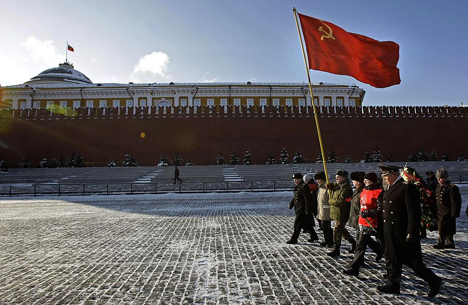 13. Русские коммунисты несут красные флаги, направляясь к мавзолею Владимира Ленина на Красной Площади. Отец Советского Союза умер 21 января 1924 года. (Misha Japaridze/Associated Press)