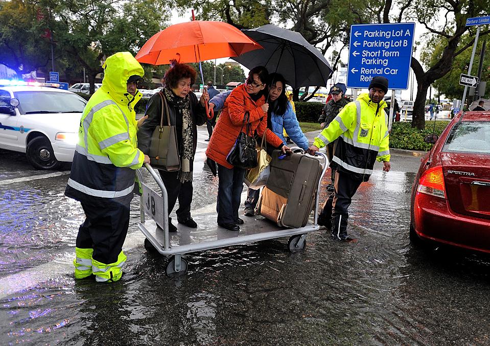 14. Работники компании «JetBlue» помогают пассажирам пересечь затопленную стоянку аэропорта в Лонг Бич, Калифорния. В этом районе идут сильнейшие ливни. (Jeff Gritchen/Long Beach Press-Telegram via Associated Press)