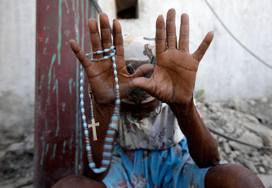 1) Женщина молится во время мессы, которую проводят рядом с руинами главного собора города в Порт-о-Пренс. Около ста человек приняли участие в воскресной мессе рядом с собором, который был полностью разрушен землетрясением во вторник. (AP Photo/Gregory Bull)