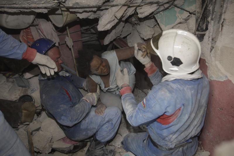 1. Российские спасатели вытаскивают гаитянку – жертву землетрясения – из-под обломков в Порт-о-Пренс 16 января 2010 года после землетрясения в 7.0 баллов. (UPI/Anatoli Zhdanov)