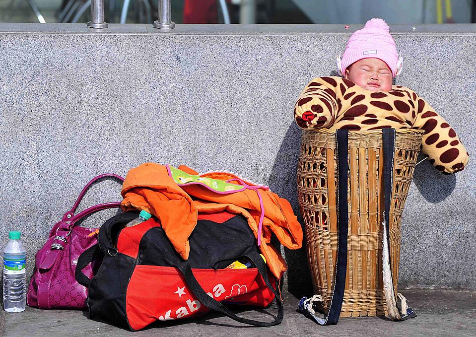 4. Закутанный в одежду ребенок ждет посадки на поезд в Нанкине, провинция Цзянсу, Китай. Китайские железные дороги ожидают огромный приток пассажиров (до 210 миллионов), так как люди едут домой на фестиваль весны. (Sean Yon/Reuters)