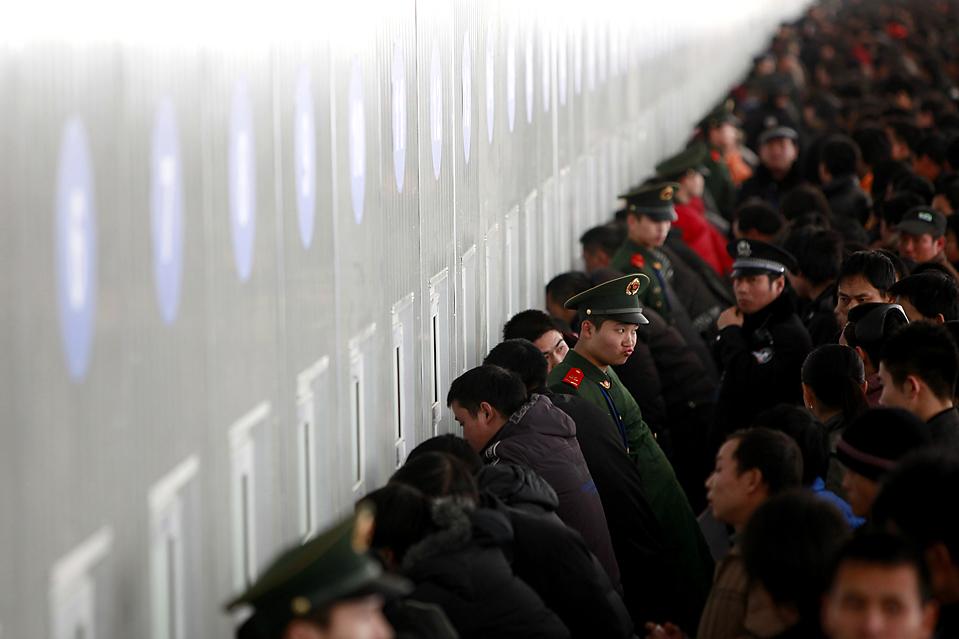 2. Военизированные полицейские следят за порядком, пока люди пытаются купить билеты на поезд на железнодорожной станции Шанхая. На фестиваль весны домой поедут около 210 миллионов пассажиров. (Aly Song/Reuters)