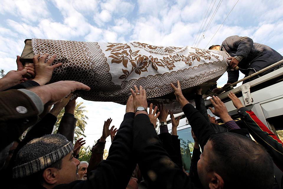 8. Люди готовятся похоронить родственника, погибшего в результате взрыва в Багдаде. Террорист-смертник убил, по меньшей мере, 21 человека, и ранил десятки других во вторник – на следующий день после взрыва в трех отелях. (Hadi Mizban/Associatd Press)