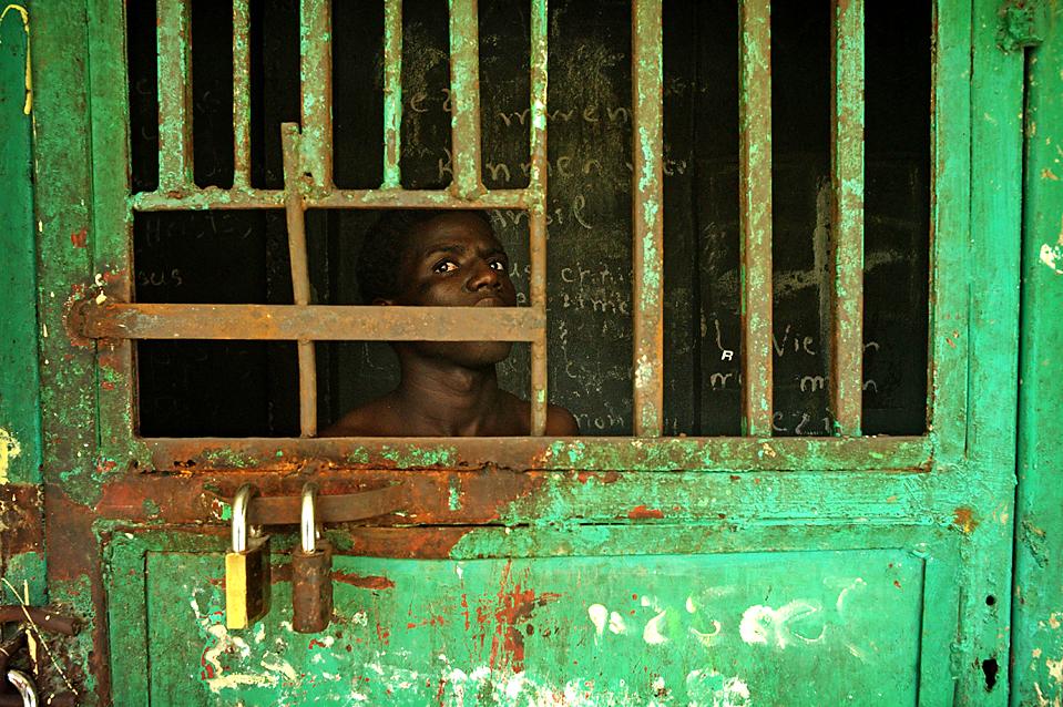 9. Мужчина выглядывает из одиночной камеры в психиатрической клинике в Порт-о-Пренс. (Olivier Laban-Mattei/Agence France-Presse/Getty Images)