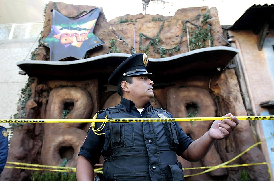 11. Полицейский охраняет вход в мексиканский бар, где в понедельник утром был ранен футболист Сальвадор Кабанас. Сейчас Кабанас в стабильном, но критическом состоянии; хирурги не смогли вытащить пулю из его черепа. Подозреваемый был задержан. (Henry Romero/Reuters)