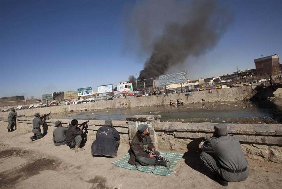 1. Афганские полицейские заняли позиции на фоне поднимающегося от торгового центра дыма после атаки боевиков организации «Талибан» в Кабуле 18 января. Талибы – некоторые в жилетах со взрывчаткой – напали на город, атаковав банки, торговый центр и правительственные здания. (Ahmad Masood / Reuters)
