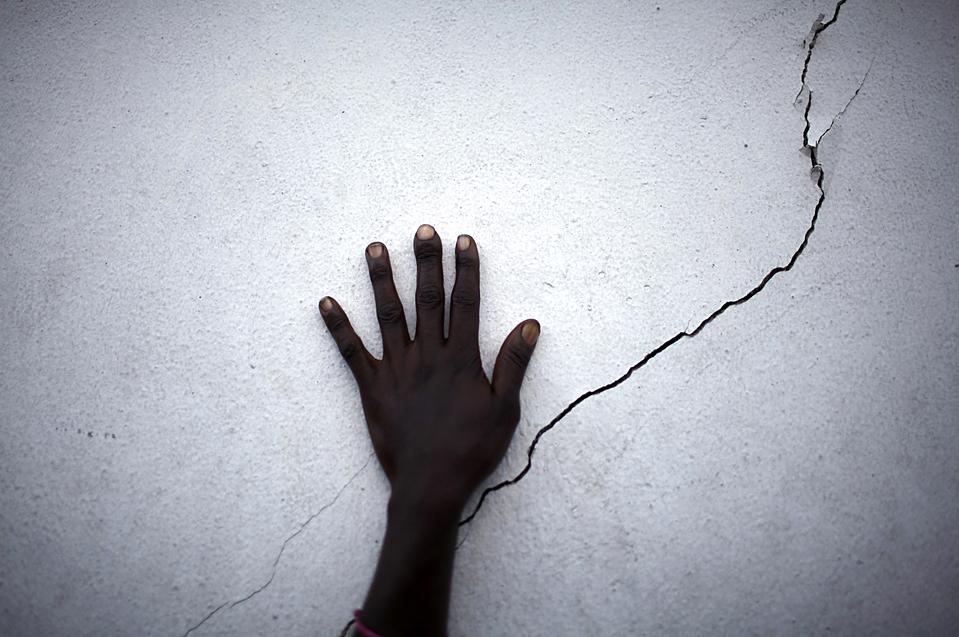 1. Женщина положила руку на треснутую стену в ожидании еды в пункте раздачи в Порт-о-Пренс. Во вторник – через две недели после крупного землетрясения в 7.0 баллов на Гаити произошло еще одно землетрясение в 4.9 баллов. (Carlos Barria/Reuters)