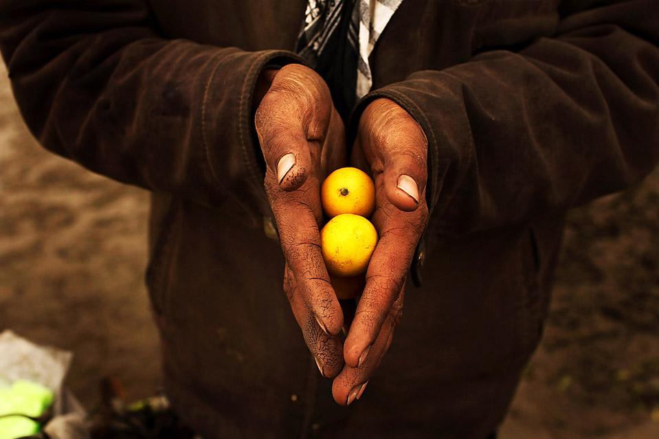 2. Торговец держит лимоны на людной торговой улице в Кабуле. А в четверг в Лондоне начнется международная конференция по вопросам Афганистана. (Spencer Platt/Getty Images)