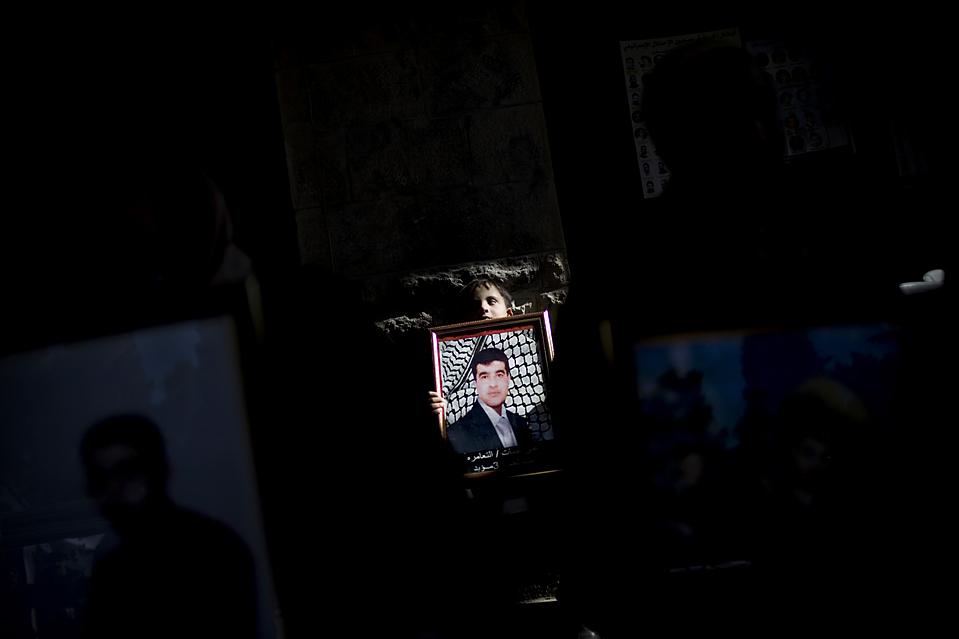 13. Палестинский мальчик держит портрет родственника, который находится в тюрьме в Израиле, во время протеста в Вифлееме. Демонстранты требовали освобождения палестинских заключенных.