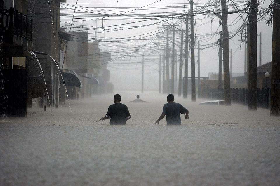 15. Люди идут по затопленной улице в Сан-Паулу, Бразилия. С 1 января более 100 человек погибло в результате оползней и наводнений, вызванных постоянными ливнями в Бразилии. (Nelson Antoine/Associated Press)