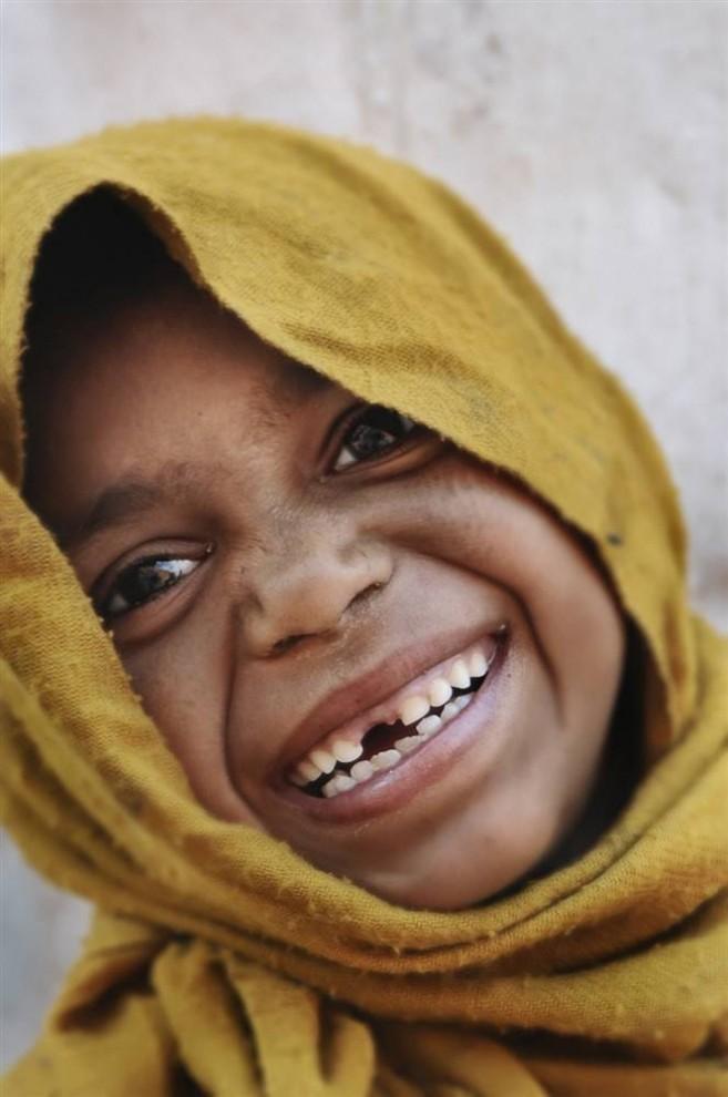 1) На этом снимке, запрокинув голову, хохочет девочка из Катманду, Непал.  (Bobby Sager / The Power of the Invisible Sun)