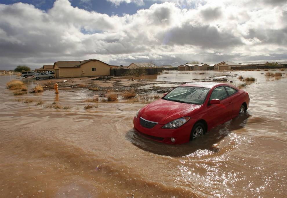 1. Оставленный автомобиль на железнодорожной станции в пятницу 22 января 2010 года в Аризоне. Аризону накрыли сильные дожди и снегопады, в результате чего пропал мальчик, предположительно унесенный поднявшимся уровнем реки, было затоплено несколько домов и оставлено несколько автомобилей. (David Kadlubowski / Arizona Republic via AP)