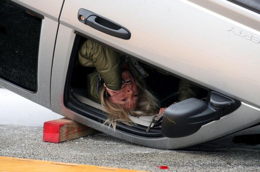 1) Неизвестная женщина висит вниз головой в своем перевернувшемся автомобиле в ожидании спасателей на эстакаде в Нью-Джерси (AP Photo/Home News Tribune, Mark R. Sullivan)
