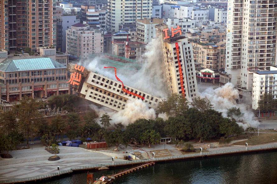 2. Половина здания падает в то время как вторая половина лишь накреняется при сносе здания для нового проекта недвижимости в Лиужоу на юге региона Гуанси. Во время взрыва рабочим удалось разъединить здание, но одна часть осталась стоять наклоненной. (AP Photo)