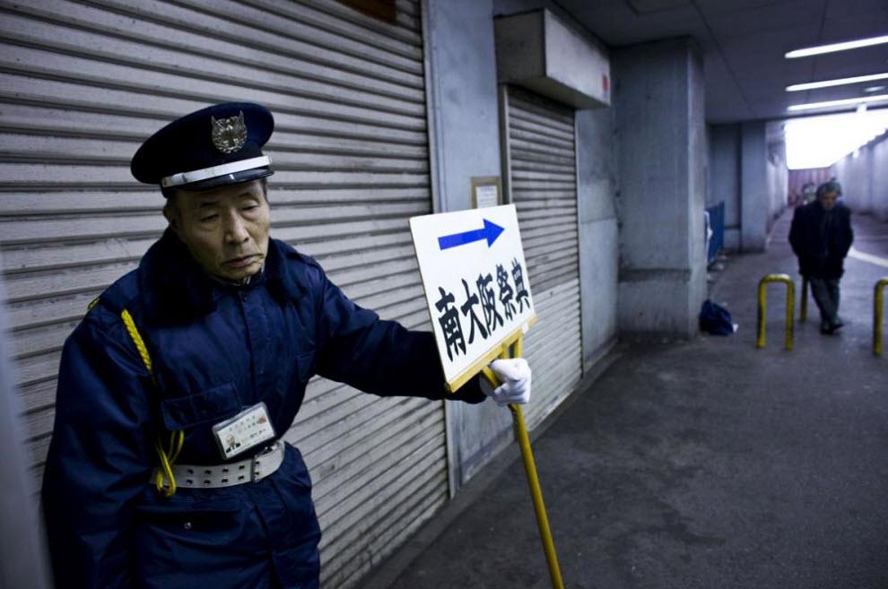 2. Пожилой человек, работающий сторожем, держит табличку похоронного бюро 18 января 2009 года в Осаке. (Shiho Fukada)