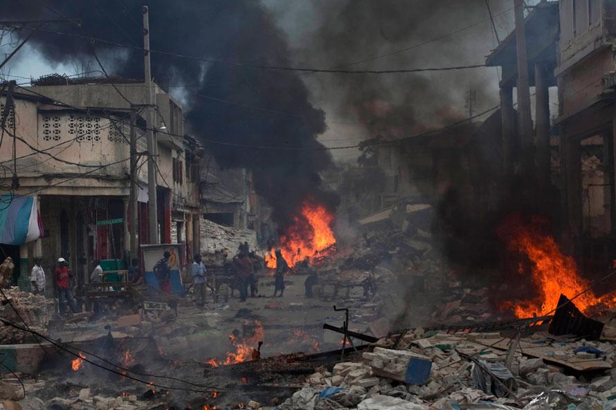 2) Люди собираются среди обломков на одной из улиц Порт-о-Пренс. (AP Photo/Ramon Espinosa)