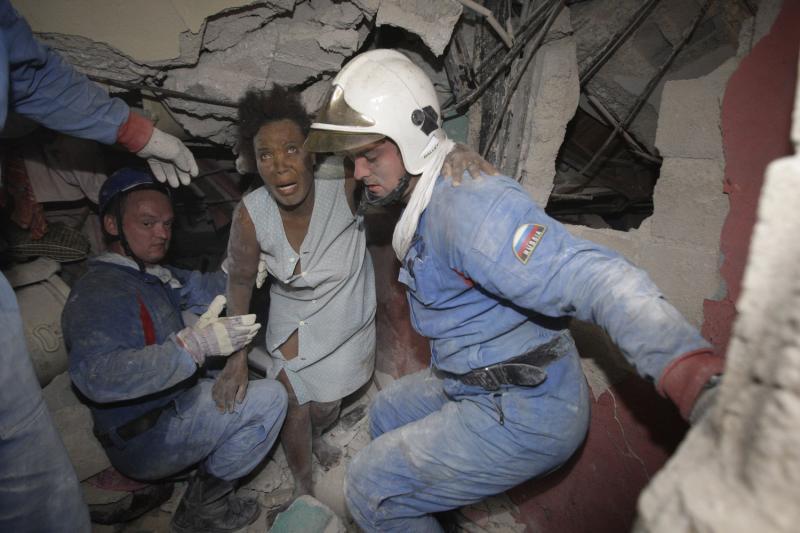 2. Российские спасатели выводят женщину из разрушенного землетрясением дома в Порт-о-Пренс 16 января. (UPI/Anatoli Zhdanov)