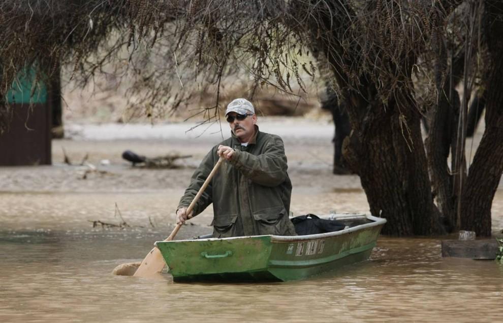 2. Тим Холидэй уплывает от своего затопленного дома 22 января 2010 года лишь с кучей одежды, которые он смог взять с собой, после того, как река Агуа Фриа вышла из берегов во время шторма в Блэк Каньон, штат Аризона. (Rob Schumacher / Arizona Republic via AP)