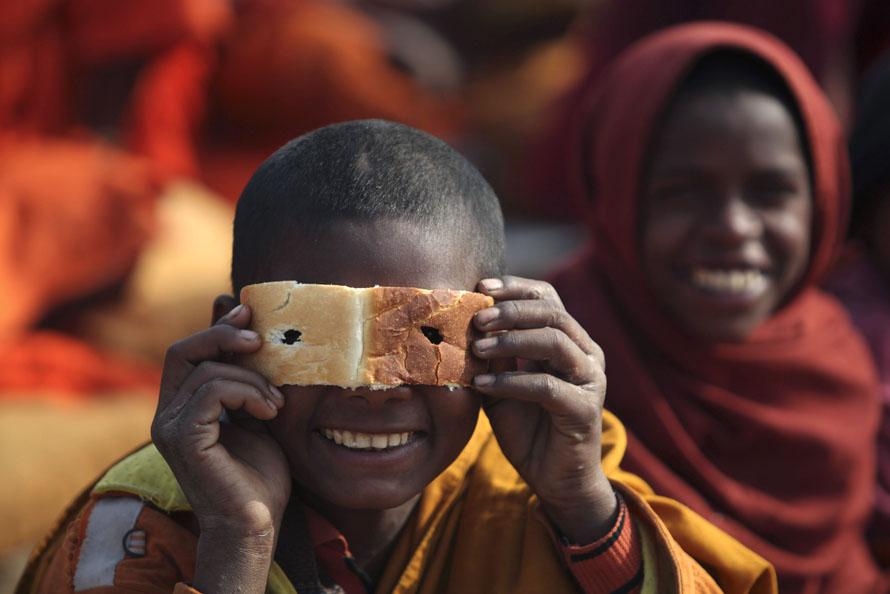 3. Индийский буддистский монах смотрит сквозь булочку, пока другие слушают лекцию Далай Ламы в храме Махабодхи в Бодх Гайя, примерно в 130 км к югу от Патны, Индия. Бодх Гайя – город, в котором к принцу Сиддхарте Гаутаме пришло просветление, и он стал Буддой. Лекции продлятся до субботы. (AP Photo/Rajesh Kumar Singh)