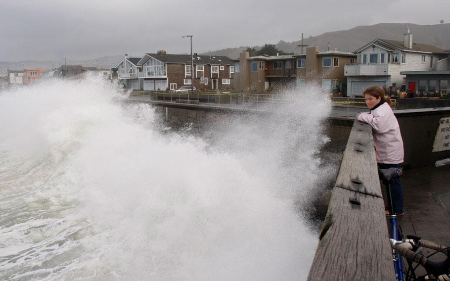 3. Ким Шульц смотрит, как большая волна разбивается о стену пирса в Пацифике, Калифорния. Огромные волны достигли берегов Калифорнии, причем некоторые из них достигали 6 метров. (AP Photo/George Nikitin)