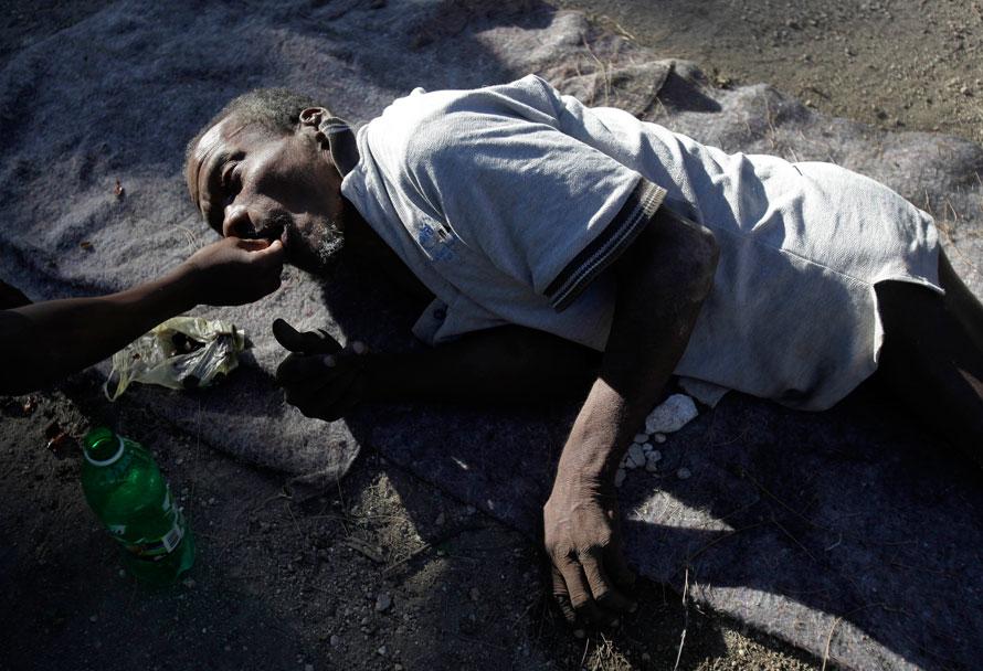 3) Старика, который лежит рядом с разрушенным зданием дома престарелых, кормят завтраком, который состоит из нескольких орехов. Более 100 стариков и старух, живут теперь возле руин дома престарелых, который был разрушен во время землетрясения во вторник. Жители дома престарелых остались без еды и ухода. Время от времени им помогают двое санитаров, которые остались с ними. (AP Photo/Julie Jacobson)