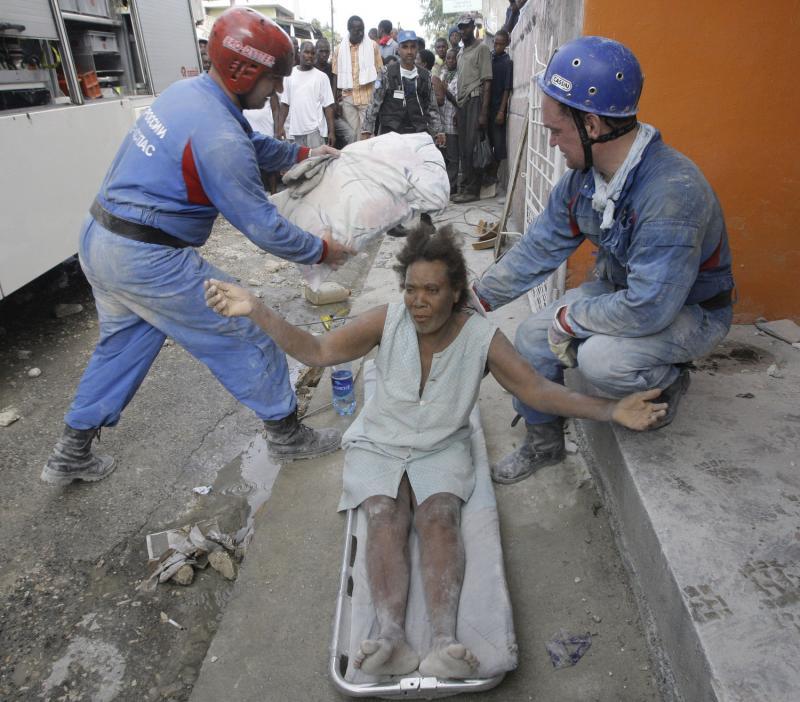 3. Российские спасатели выносят женщину, спасенную ими из-под обломков дома, в Порт-о-Пренс 16 января после землетрясения. (UPI/Anatoli Zhdanov)