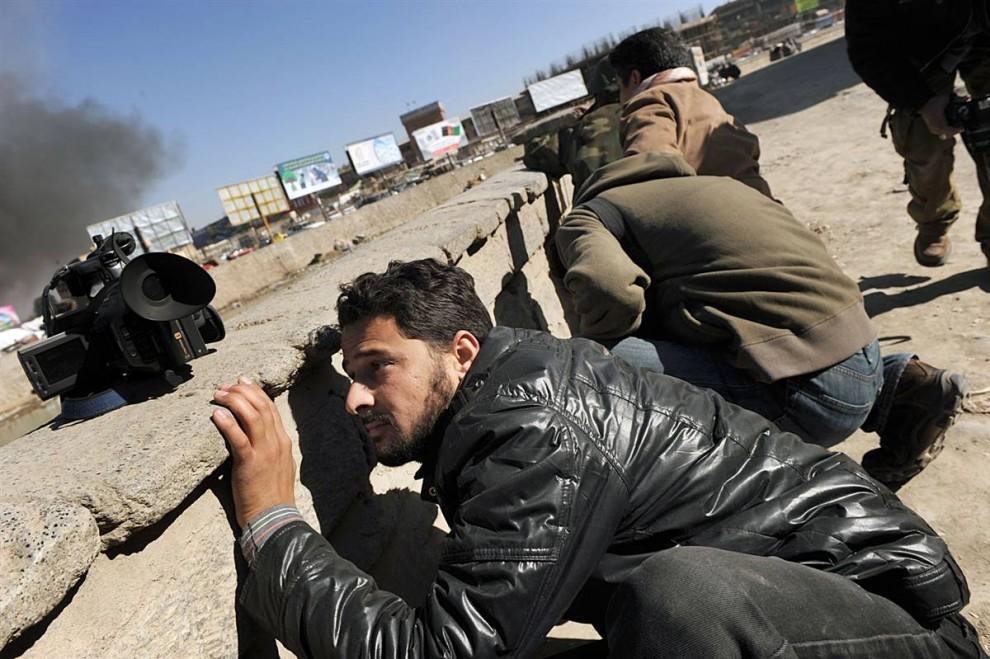 3. Афганский журналист прикрывается на месте перестрелки между боевиками «Талибана» и полицейскими в сердце Кабула в понедельник. (Shah Marai / AFP - Getty Images)