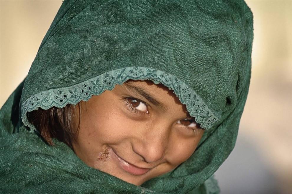 3) Несмотря на то, что эта малышка живет в лагере вынужденных переселенцев в Северо-западной пограничной провинции  Пакистана, она не разучилась улыбаться. (Bobby Sager / The Power of the Invisible Sun)
