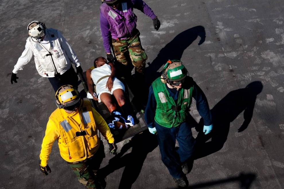 3. Спасатели несут жертву землетрясения на борт плавучего госпиталя «Comfort». (Brendan Hoffman / Getty Images)