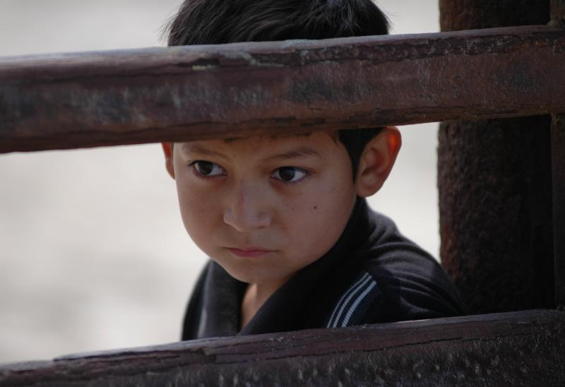 3. Мальчик мексиканец смотрит через забор на границе Мексики с Калифорнией во время митинга, организованного ради протеста против завершения тройного забора на границе между Калифорнией и Баджа Калифорнией. (UPI Photo / Earl S. Cryer)