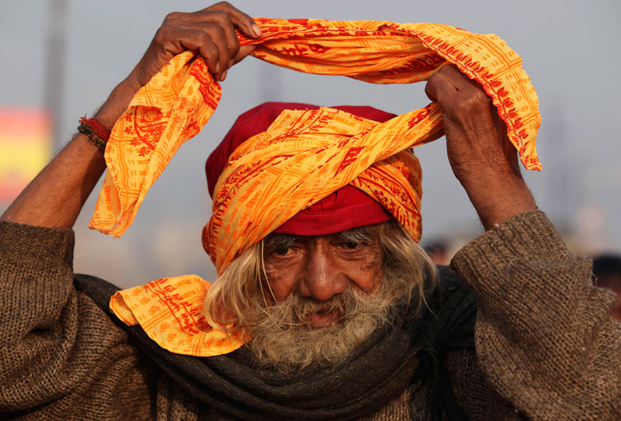 3)  Садху завязывает тюрбан, сидя на берегах Сангама, слияния рек Ганги и Ямуны, во время ежегодной ярмарки Магх Мела в Аллахабаде, Индия. (AP Photo/Rajesh Kumar Singh)