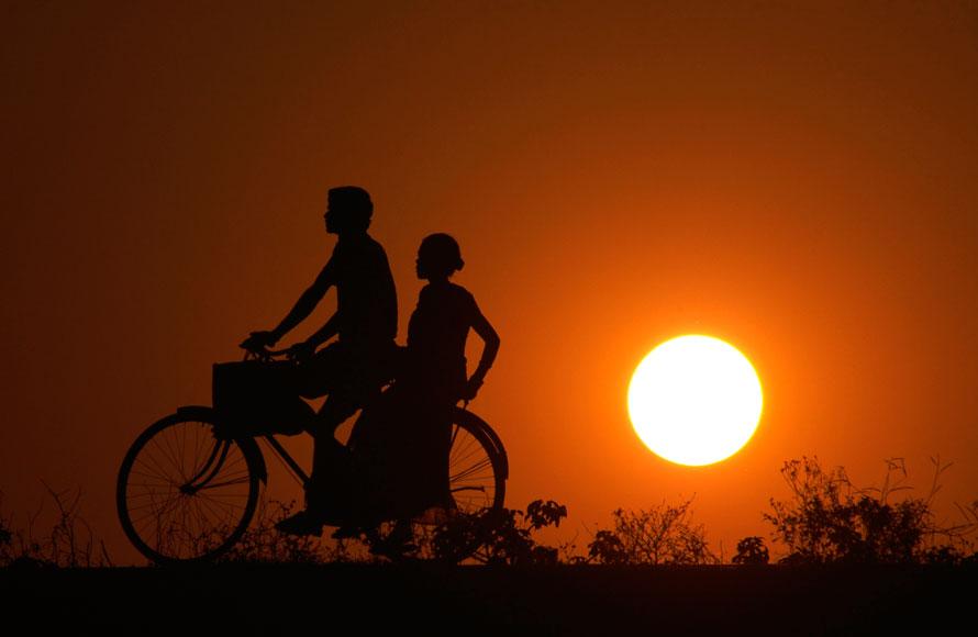 4. Мужчина и женщина возвращаются в деревню после рабочего дня на велосипеде на фоне заката в конце года на окраинах Пури, Индия. (AP Photo/Biswaranjan Rout)