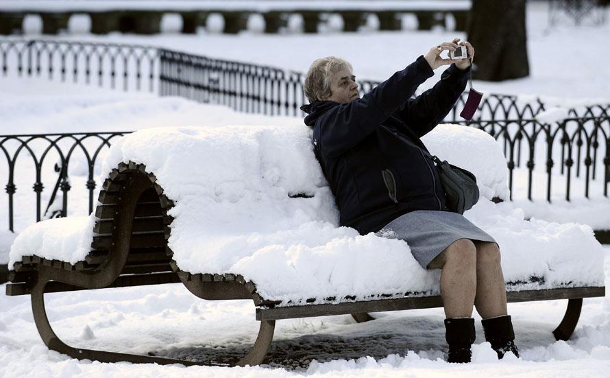 4. Женщина фотографирует себя на скамейке в занесенном снегом парке баскского города  Витория на севере Испании. В этом регионе бушует ледяной ветер, во многих частях Испании зарегистрированы низкие температуры и снежные бури. (AP Photo/Alvaro Barrientos)
