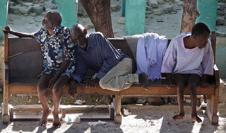 4) Два старика и инвалид сидят на скамейке у своего разрушенного дома престарелых в Порт-о-Пренс. (AP Photo/Julie Jacobson)