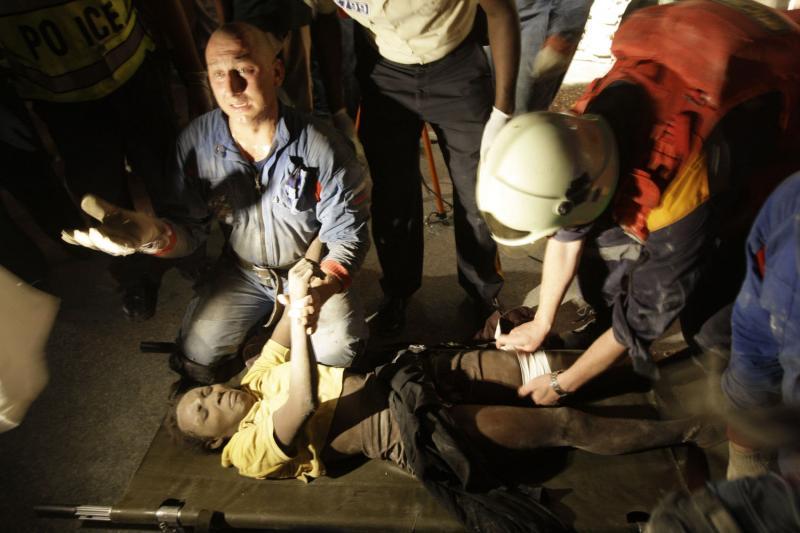 4. Российские спасатели предоставляют медицинскую помощь жертве 7-балльного землетрясения у разрушенного дома в Порт-Пренс 16 января 2010 года. (UPI/Anatoli Zhdanov)
