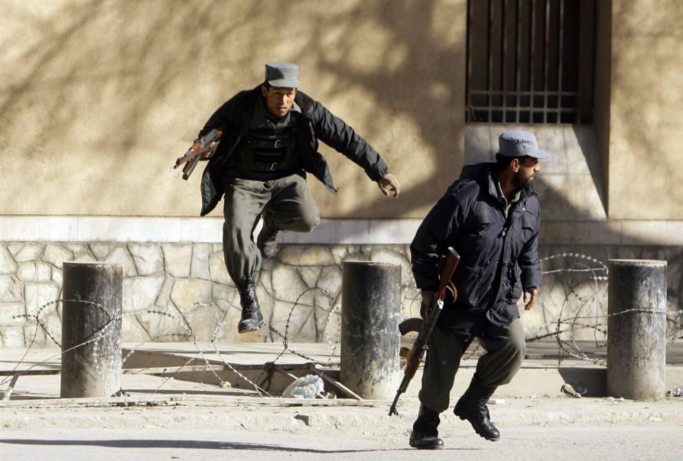 4. Афганские полицейские бегут во время перестрелки с боевиками в понедельник. Взрывы и пулеметные очереди грохотали в городе несколько часов. (Omar Sobhani / Reuters)