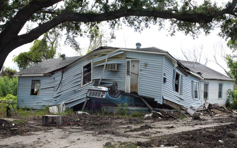 4) Дом стоит на автомобиле на улице Lower 9th Ward в Новом Орлеане 27 августа 2006 года. Спустя год после прорыва дамбы после урагана Катрина, в результате которого вода поднялась по самые крыши, город по-прежнему лежал в руинах. (UPI Photo/A.J. Sisco)