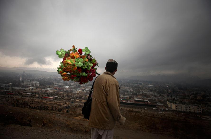 4) Хикмет, афганский торговец искусственными цветами, стоит на вершине холма над Кабулом. (AP Photo/Altaf Qadri)