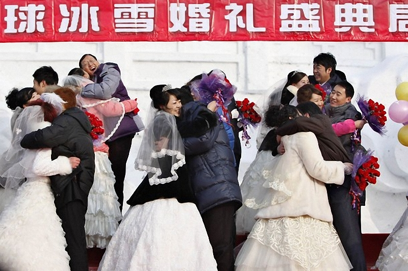 2) Молодожены обнимаются на фоне снеговой скульптуры, изображающей пекинский Храм Неба. (REUTERS/Aly Song)