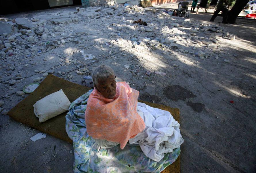 5) Женщина сидит на развалинах своего дома престарелых в Порт-о-Пренс, разрушенного землетрясением во вторник. (AP Photo/Julie Jacobson)