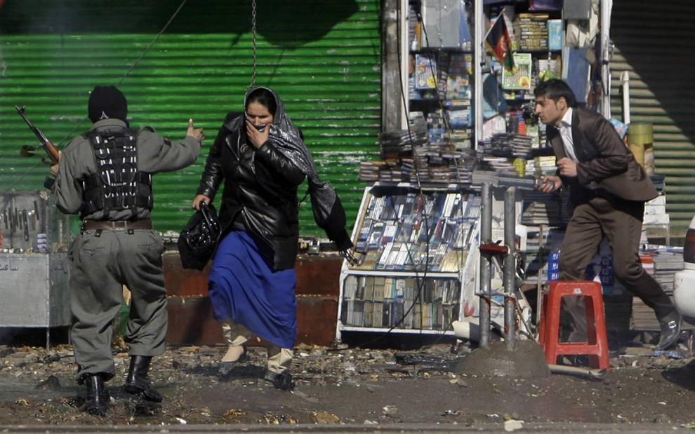 5. Афганский полицейский помогает эвакуировать мирных жителей во время перестрелки с боевиками организации «Талибан» в понедельник. В столице афганские войска окружили здание кинотеатра и открыли огонь по находившимся внутри боевикам. (Omar Sobhani / Reuters)