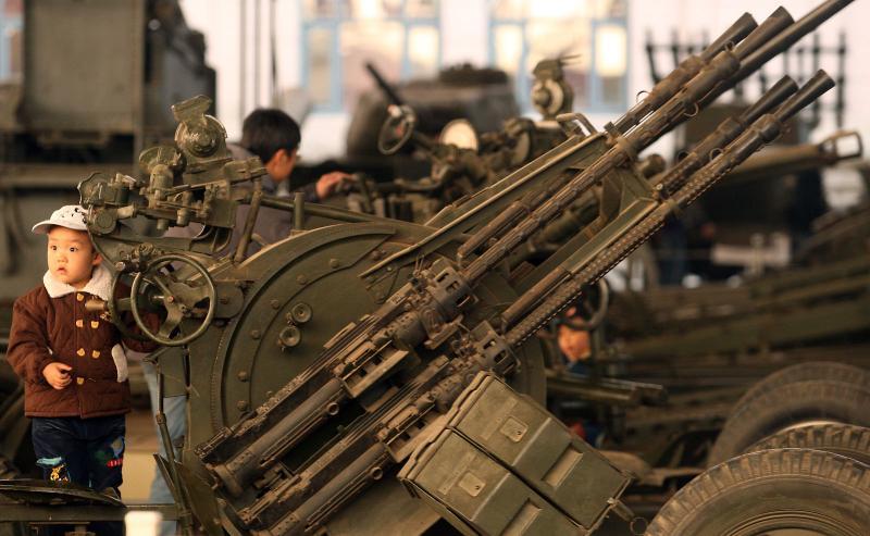 5. Китайский мальчик стоит у старой зенитки в Национальном военном музее революции в Пекине 22 марта 2009 года. Объединённое командование вооружённых сил США в зоне Тихого океана заявило, что «агрессивное поведение Китая» с невооруженным американским судном показывает, что Пекин еще не готов вести себя адекватно. (UPI Photo/Stephen Shaver)