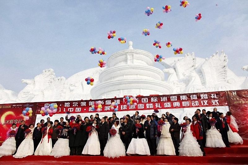 11) Женихи и невесты все вместе позировали фотографам на фоне снежной скульптуры, изображающей знаменитый пекинский Храм Неба. (REUTERS/Aly Song)
